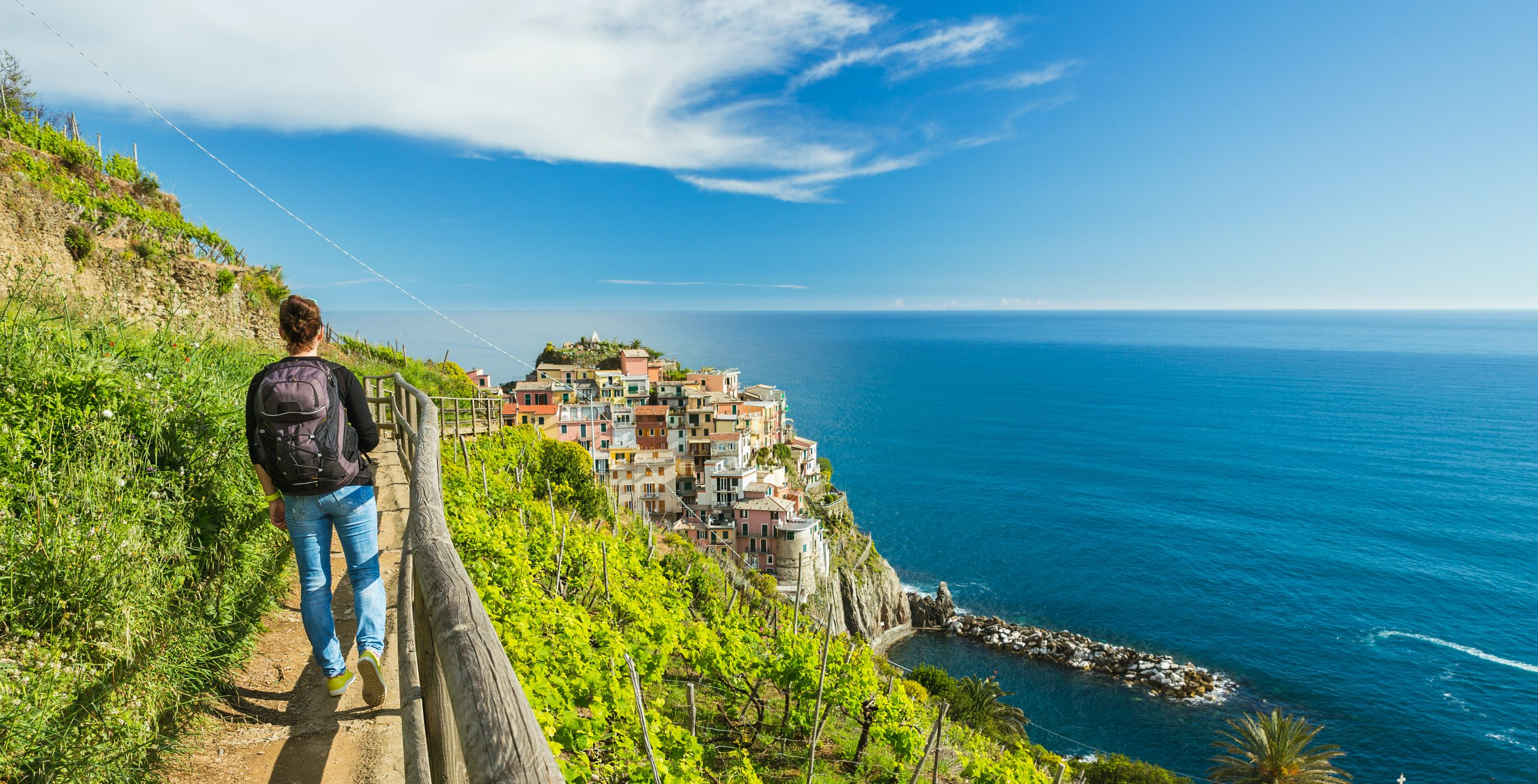 Woman walking on hiking trail in Cinque Terre, Italy